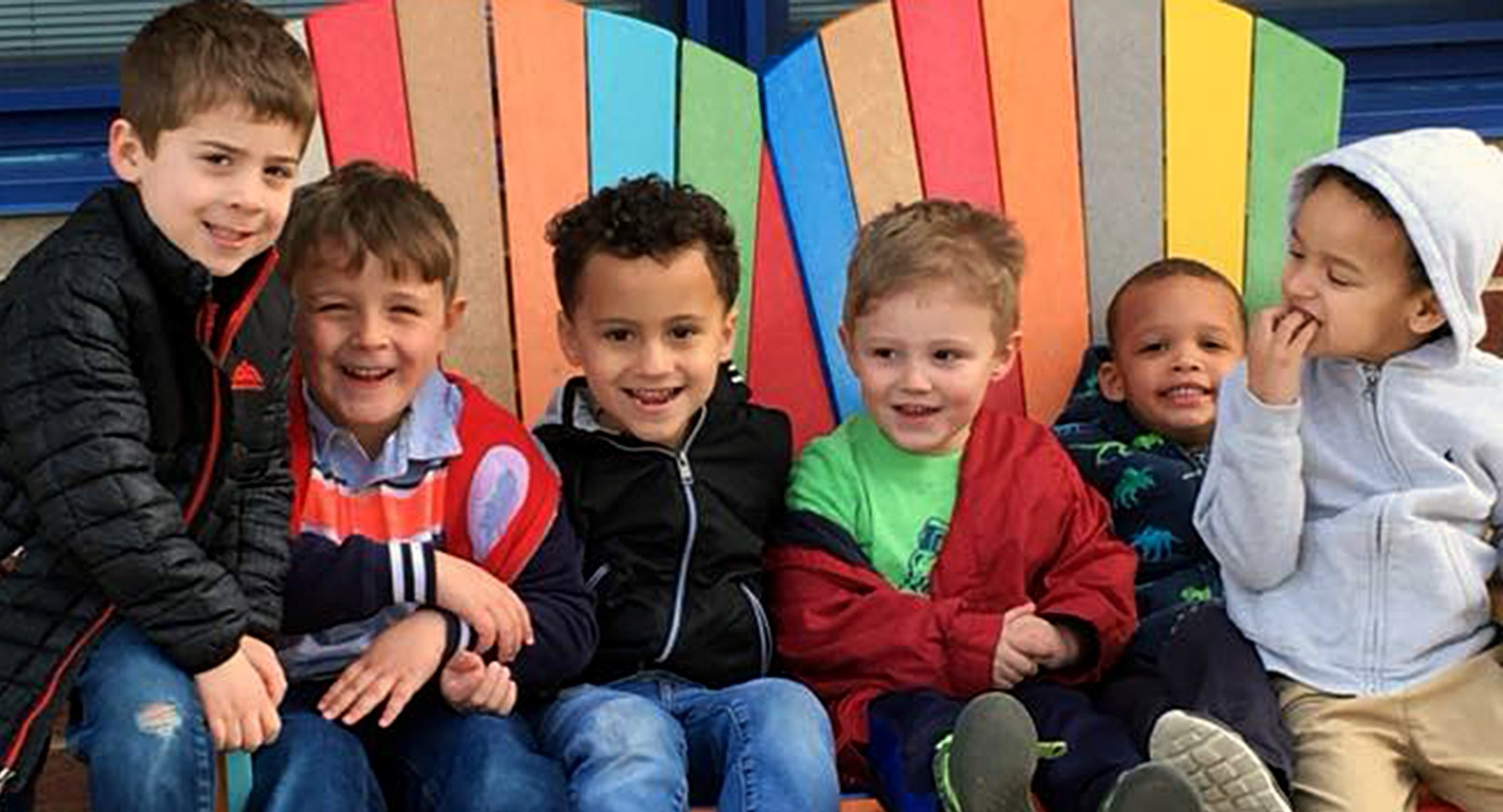 Young kids in colorful wooden chairs