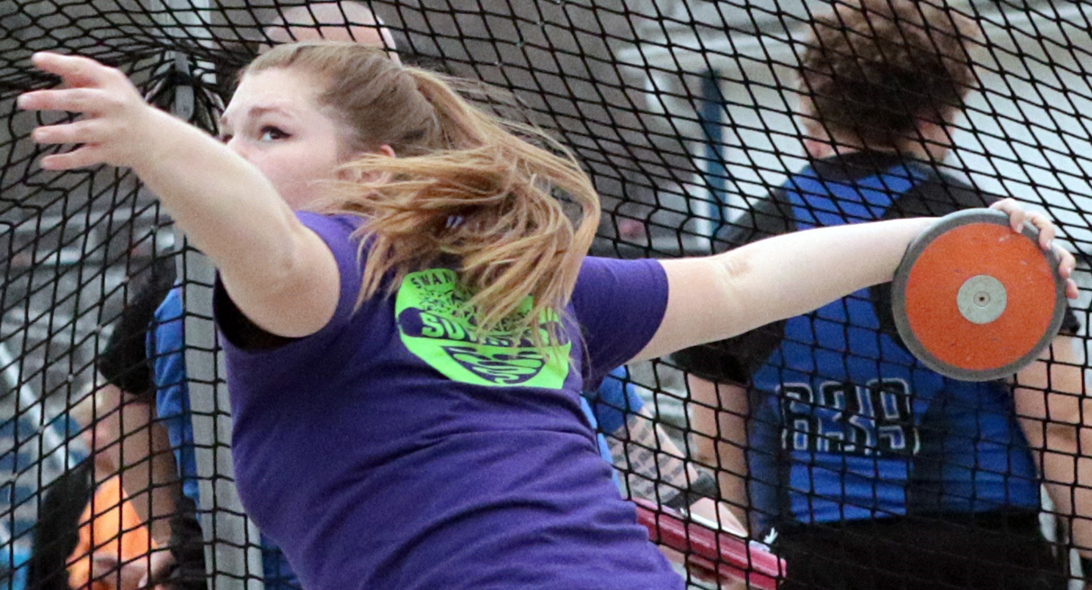 Girl in purple shirt throwing the discus