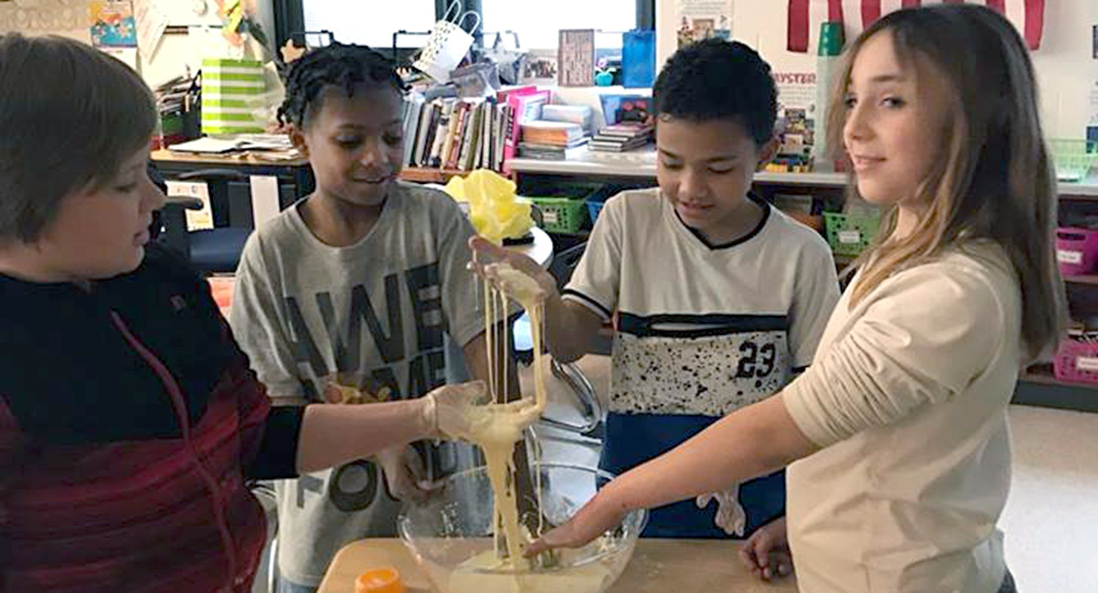 Kids mixing ingredients in a mixing bowl