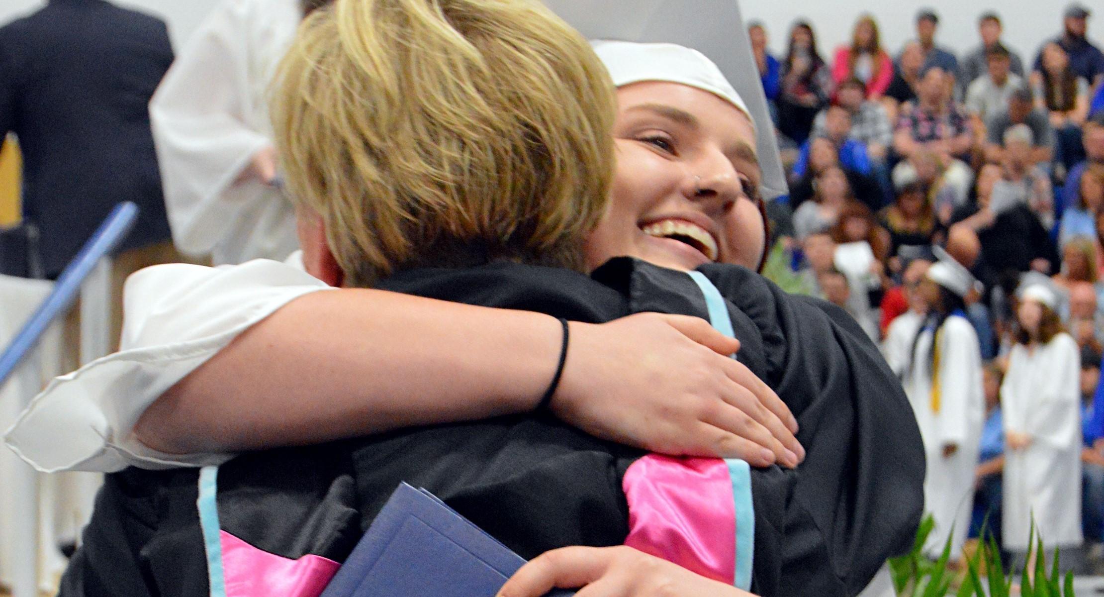 girl grad hugging principal
