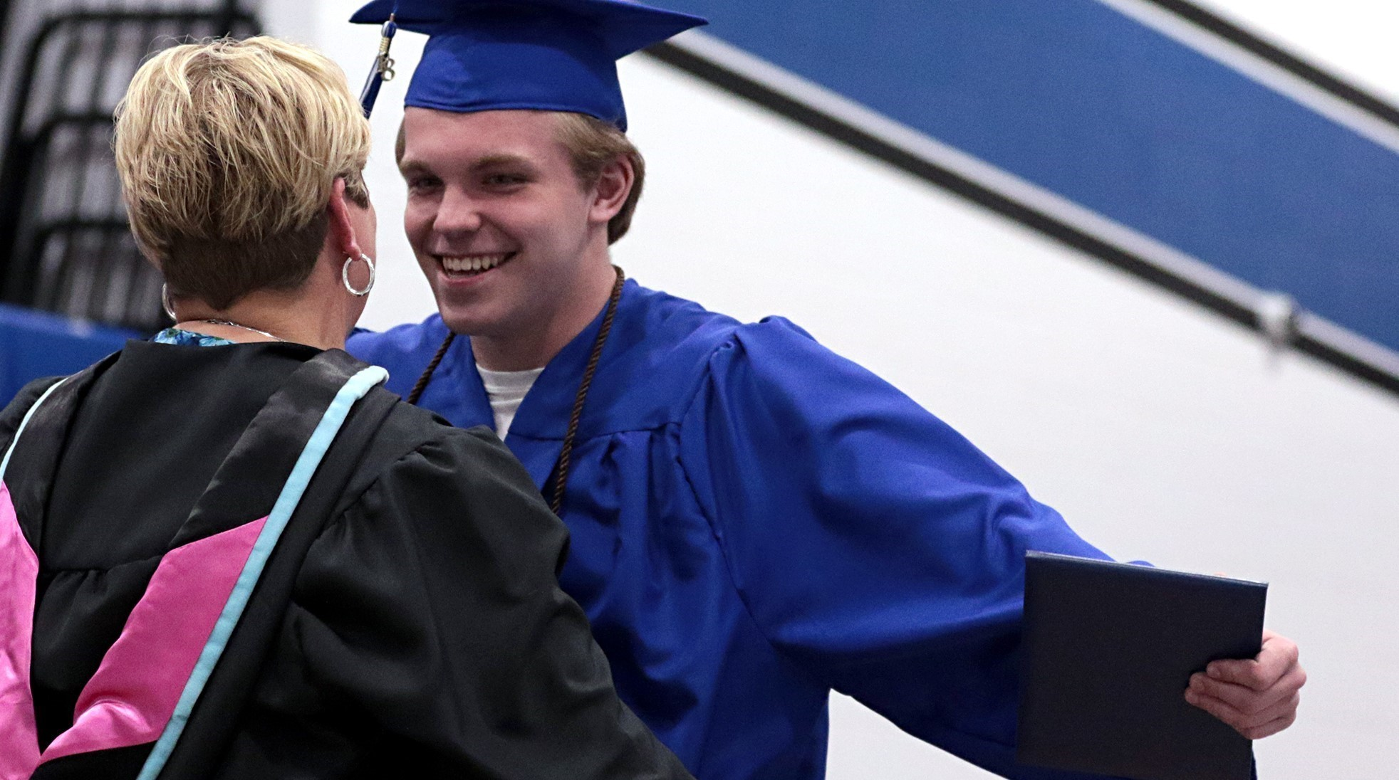 boy graduate preparing to hug principal