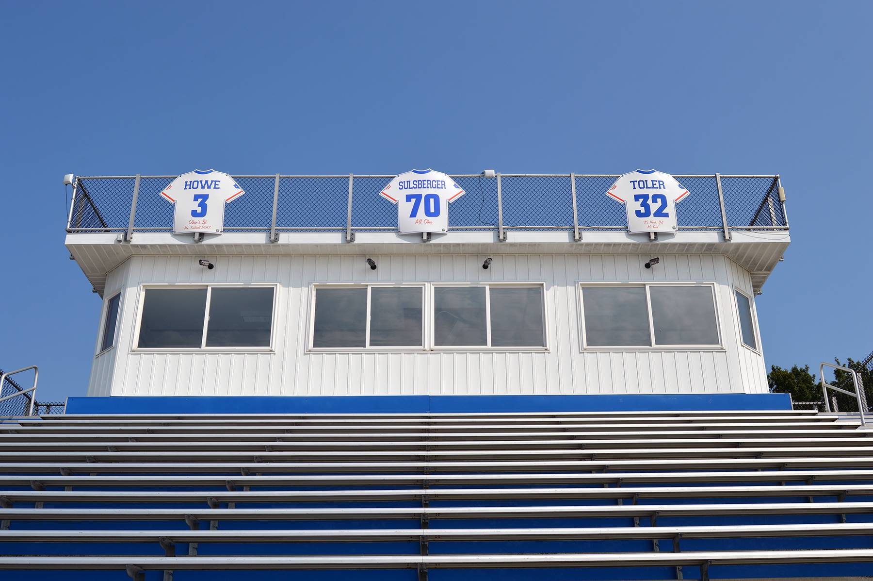 The Grant & Valerie Hickman Press Box on the visitors stands, with three signs representing the reti